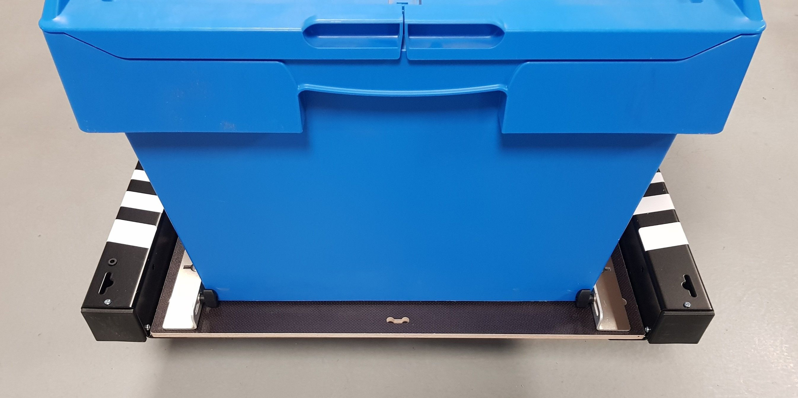 Blue box on a tray of a trailer with a black frame and three white stripes on each side